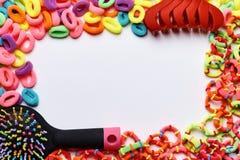 Een kader van multi-colored kleurrijke elastiekjes voor haar, kammen en haarklemmen stock foto's