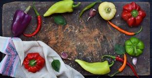 Een kader voor recept van verschillende verscheidenheden van zoete en hete peper op een houten achtergrond Voedselgrens De ruimte Royalty-vrije Stock Afbeeldingen