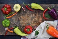 Een kader voor recept van verschillende verscheidenheden van zoete en hete peper op een houten achtergrond Voedselgrens De ruimte Stock Afbeelding