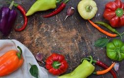 Een kader voor recept van verschillende verscheidenheden van zoete en hete peper op een houten achtergrond Voedselgrens De ruimte Royalty-vrije Stock Foto