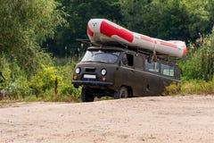 Een kaki minibus draagt een opblaasbare rubber rafting boot op de boomstam stock foto's