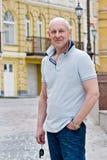 Een kale glimlachende mens op middelbare leeftijd houdt een autosleutel royalty-vrije stock afbeelding