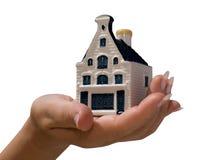 Een kalende hand een stuk speelgoed huis Stock Afbeeldingen