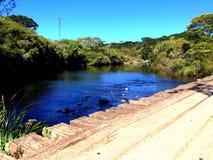Een kalme rivier omhoog van een houten brug Stock Fotografie