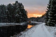 Een kanaal met een sneeuwweg en een rode hemel Royalty-vrije Stock Foto