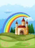 Een kasteel bij de heuveltop met een regenboog Stock Afbeelding