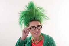Een Kaukasisch meisje in een groene kleding en met groen haar treft voor de vakantie voorbereidingen Kostuum van de leraar van pr Stock Foto's