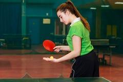 Een Kaukasisch vijftien-jaar-oud donkerbruin meisje maakt een bal in pingpong werpen De peddel van het Pingpong van de pingpong royalty-vrije stock fotografie