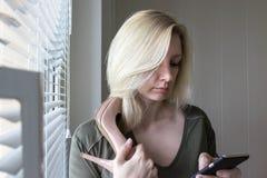 Een Kaukasische blonde vrouw zich dichtbij het venster met een hoge hielschoen bevinden en surfend Internet die in haar smaryphon stock foto