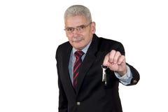 Een Kaukasische hogere manager die een sleutel aanbiedt Royalty-vrije Stock Foto
