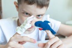 Een Kaukasische jongen die verschillende rollen spelen door handpoppen, speelgoed voor het uitdrukken van zijn emoties, agressie, stock foto's