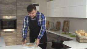 Een Kaukasische mannelijke kok met een baard bereidt voedsel in een moderne keuken voor, de pasteitjes van de grillshamburger, ti stock videobeelden