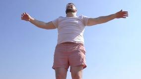 Een Kaukasische mens met een baard is bezig geweest met dynamische yoga op de banken van de rivier, een zandig strand, een uitbre stock videobeelden