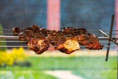 Een kebab op een vleespen wordt omgekeerd hangt over een brand die Dit heerlijke voedsel kijkt smakelijk stock afbeelding