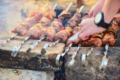 Een kebab van mensengebraden gerechten op vleespennen en snijdt vlees met een mes, barbecue met uien, paddestoelen en vlees af royalty-vrije stock fotografie