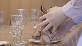 Een kelner schikt het servet op de plaat stock video