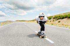Een kerel die een helm en zonnebril dragen berijdt zijn longboard op een landweg Stock Foto's