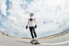 Een kerel die een helm en zonnebril dragen berijdt zijn longboard op een landweg Royalty-vrije Stock Foto