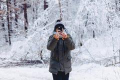 Een kerel die langs een snow-covered weg dichtbij een pijnboombos lopen met telefoon royalty-vrije stock afbeeldingen