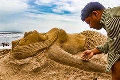 Een kerel die een standbeeld van het meerminzand in zandig seabeachart. maken royalty-vrije stock fotografie