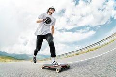 Een kerel in een helm en zonnebril versnelt het duwen van zijn voet op zijn longboard Stock Afbeelding