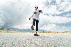 Een kerel in een helm en zonnebril versnelt het duwen van zijn voet op zijn longboard Stock Foto
