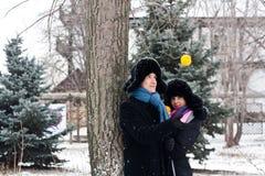 Een kerel en een meisje bij de boom met sinaasappel Stock Fotografie