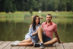 Een kerel en een meisje genieten van elkaar in een romantische atmosfeer, zitten op de pijler stock foto