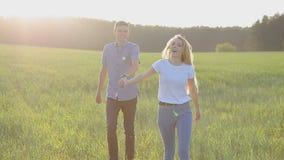 Een kerel en een meisje lopen op het gras, houdend handen stock footage