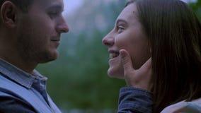 Een kerel en een meisje onderzoeken elkaar de ogen van ` s de kerel houdt de meisjes` s handen achter zijn gezicht Sluit omhoog stock videobeelden