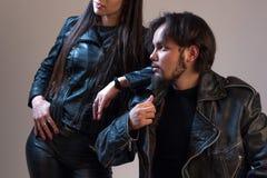 Een kerel en een meisje in zwarte leerjasjes De reclame van kleren voor rotsventilators De fotografie van de studio Musical of fi Stock Afbeeldingen
