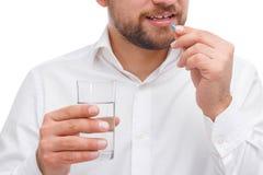 Een kerel houdt een glas water en staat een capsule in zijn handclose-up op een wit geïsoleerde achtergrond te drinken op het pun Stock Foto