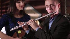 Een kerel in een jasje en een overhemd speelt de fluit, en een mooi brunette in een blauwe kleding spelend een gitaar Twee mensen stock video