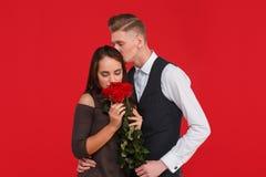 Een kerel kust een meisje in het hoofd dat rozen op een rode achtergrond ruikt Royalty-vrije Stock Fotografie