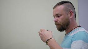 Een kerel met een baard en een mohawk het drinken puer thee van een kom stock videobeelden