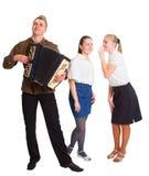 Een kerel met een harmonika en twee meisjes royalty-vrije stock afbeelding