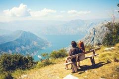 Een kerel met een meisje zit op een bank in Kotor-Baai Gelukkige familie van vier die in de bergen lopen Het concept van de famil stock afbeelding