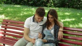Een kerel met een meisjeszitting op een bank en horlogebeelden op telefoon stock video