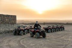 Een kerel met een gesloten zakdoek op zijn gezicht zit op een vierlingfiets tegen de achtergrond die van de zon over de woestijn  stock foto