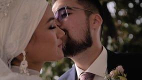 Een kerel met glazen en een baard kust zacht zijn meisje op de wang Een zeer mooi jong paar stock footage