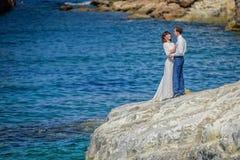 Een kerel met een meisje die zich op de rotsen dichtbij het overzees bevinden stock afbeeldingen
