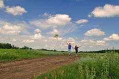 Een kerel met een meisje lanceert een vlieger op het gebied Royalty-vrije Stock Afbeelding