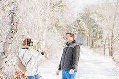 Een kerel met een meisje in een snow-covered bos het meisje werpt sneeuw bij de kerel, emoties royalty-vrije stock fotografie