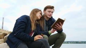 Een kerel met een meisje zit op de de rivierbank en het drinken thee stock videobeelden