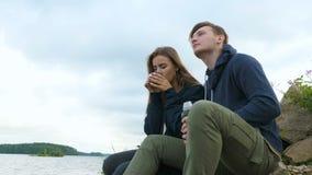 Een kerel met een meisje zit op de de rivierbank en het drinken thee van een thermosfles stock footage