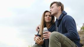 Een kerel met een meisje zit op de de rivierbank en het drinken thee van een thermosfles stock video