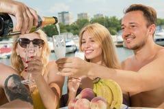 Een kerel met twee meisjes drinkt champagne op een jacht stock foto's