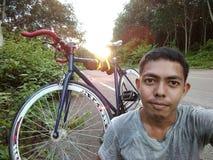 een kerel met zijn fiets op de weg Royalty-vrije Stock Afbeelding