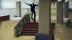 Een kerel op een skateboard aan het glijden op het spoor stock footage