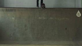 Een kerel op een skateboard beweegt zich neer van de helling stock video
